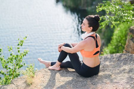 Content calm young woman in sportswear sitting on edge of quarry Stockfoto