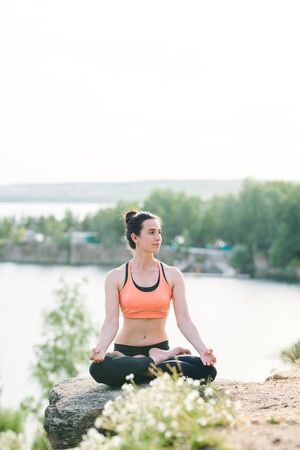 Content female yogis in sports bra sitting in lotus position