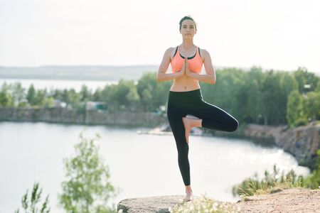 Peaceful fit woman standing on one leg on quarry stone Stockfoto