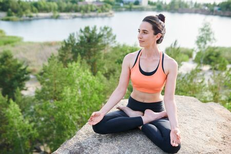 Content relaxed young lady in sportswear sitting with crossed legs on stone Stockfoto