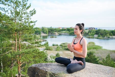 Serious calm young girl sitting in lotus position on stone at lake Stockfoto