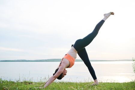 Three-legged downward-facing dog pose on river bank