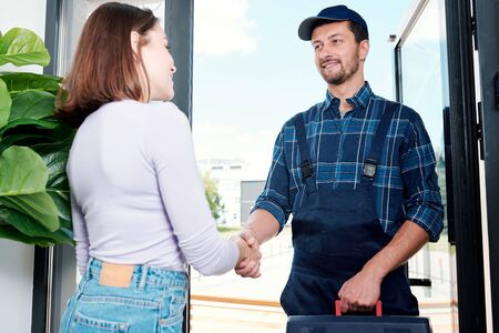 Happy young technician in workwear shaking hand of housewife