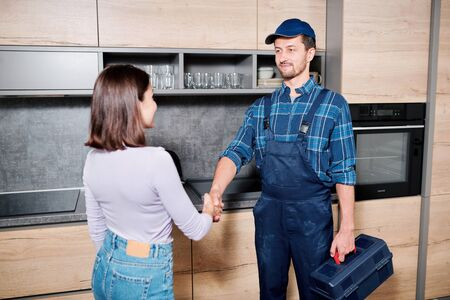 Young master of household maintenance service shaking hand of housewife