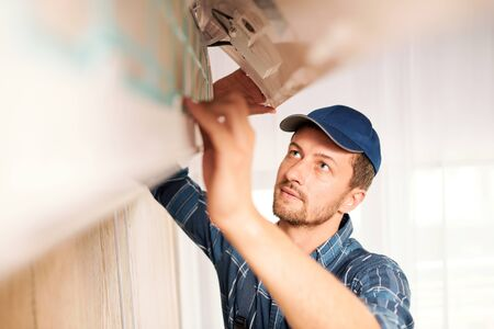 Young workman in workwear trying to find out reason of air conditioner disorder