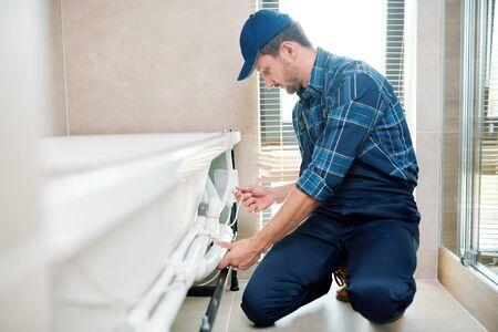 Zeitgenössischer Techniker in Arbeitskleidung, der das Rohrsystem durch die Badewanne installiert