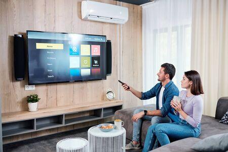 Giovane coppia che prende il tè mentre va a guardare qualcosa sul pannello della tv al plasma
