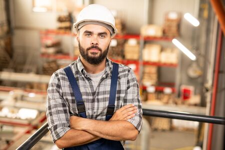 Young confident contractor or engineering staff looking at you in warehouse Stock Photo