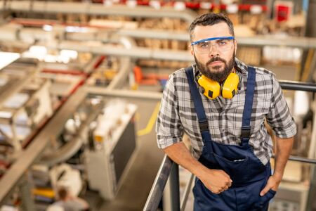 Serious technician of large factory in protective eyeglasses and headphones Stockfoto