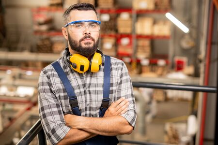 Serious warehouse worker in protective eyewear and headphones