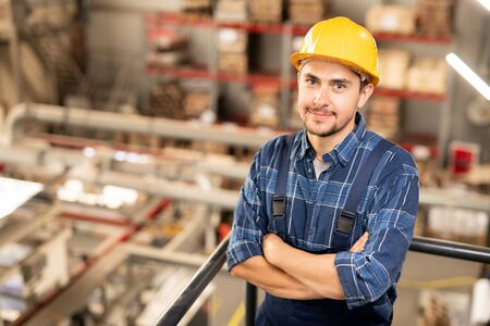 Young successful engineer in hardhat and uniform crossing his arms by chest Stock Photo
