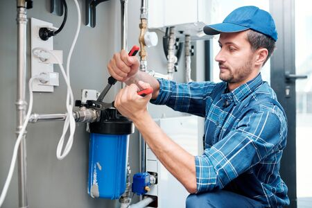 Young plumber or technician installing or repairing system of water filtration Stock Photo