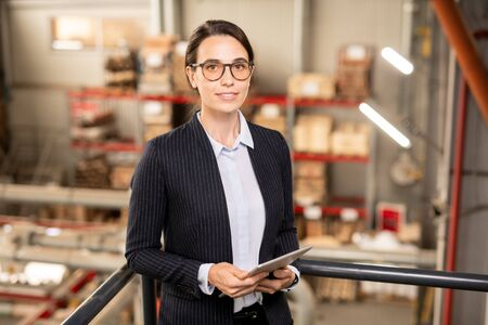 Pretty young professional with touchpad standing in warehouse Reklamní fotografie