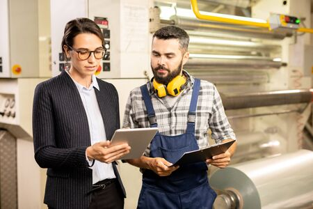 Two young engineers testing new system of quality control in chemical factory Stock Photo