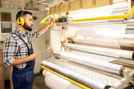 Serious young engineer of chemical production factory taking control of machine Imagens