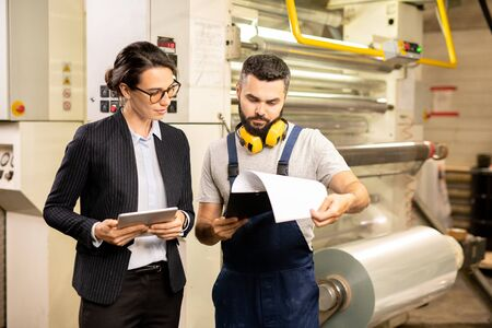 Two factory workers reading document with description of new technical equipment Stock Photo