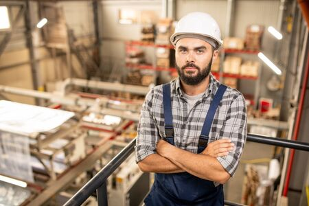 Young bearded foreman in overalls and hardhat crossing arms by chest