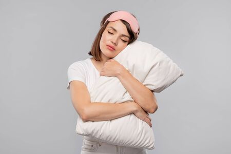 Young tranquil female embracing pillow while keeping her head on it