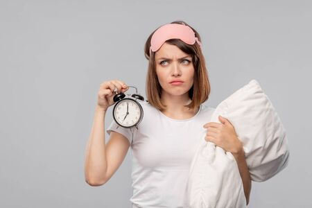 Displeased young woman with pillow holding alarm clock showing 7 am