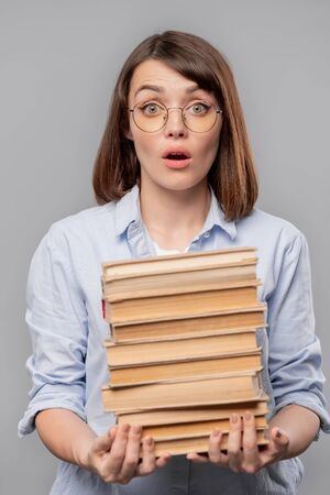 Young surprised teacher or student with stack of books