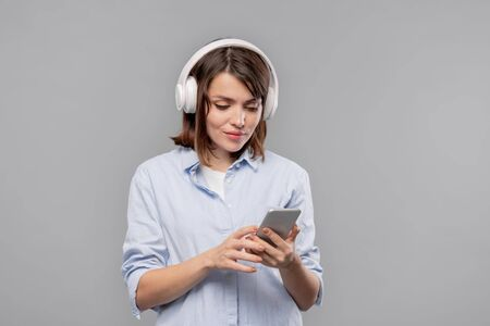 Pretty casual girl with smartphone and headphones scrolling through playlist