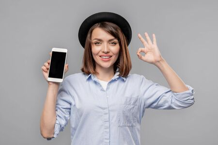 Young casual woman showing okay gesture and promo of seasonal sale