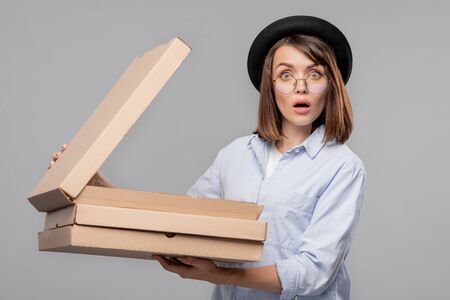 Astonished young woman in casualwear opening one of carton boxes Imagens