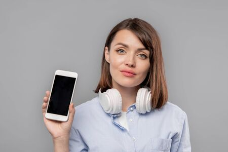 Pretty girl with headphones showing you advert or promo on smartphone screen Фото со стока