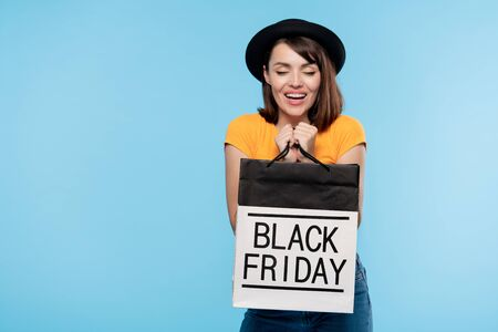 Cute brunette girl in hat and t-shirt holding black friday paperbag