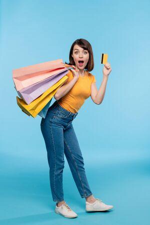 Junge weibliche Shopaholic in Freizeitkleidung, die mit Kreditkarte prahlt