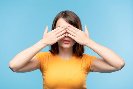 Young brunette female in yellow t-shirt covering her eyes with hands