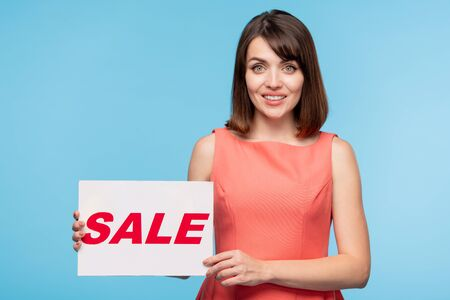 Gorgeous young woman holding paper poster with sale announcement