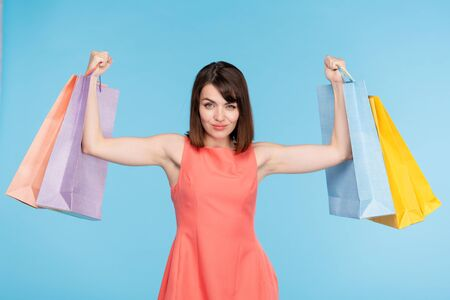Young brunette female shopper lifting paperbags after successful shopping Stock Photo