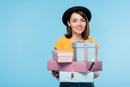 Pretty shopper holding stack of packed and wrapped gifts for holiday