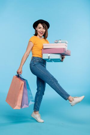 Young cheerful shopper in casualwear carrying gifts and paperbags