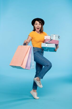 Young excited shopaholic with giftboxes and paperbags