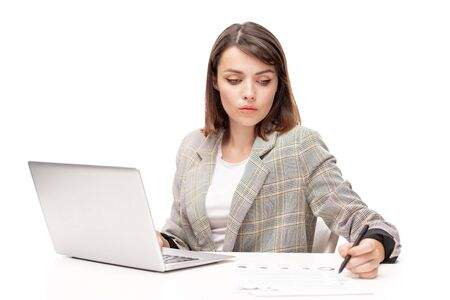 Young serious female broker reading financial paper in front of laptop Stok Fotoğraf