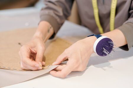 Hands of young seamstress pinning cut sketch to textile while working over new model of clothes in workshop Stock Photo