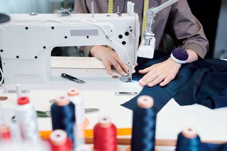 Female tailor hands moving piece of blue textile while sewing clothes by machine in workshop