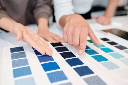 Young male and female fashion designers pointing at color swatches of textile and choosing one for new order of client