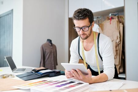 Young confident fashion designer with tablet scrolling through online ideas