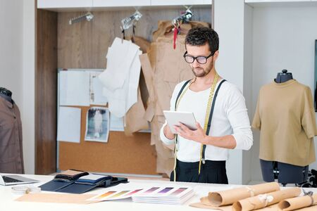Young tailor in casualwear surfing through websites of fashion trends