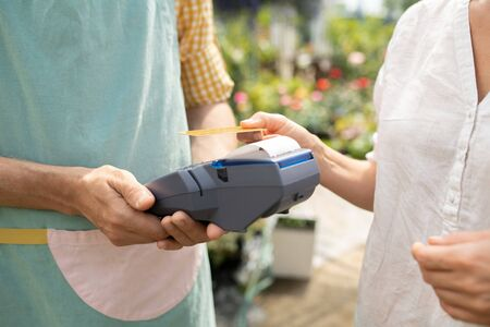 Young client of garden center paying for her purchase by credit card Banco de Imagens