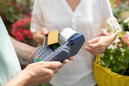 Acheteur féminin contemporain utilisant une carte de crédit pour payer des fleurs fraîches en pot Banque d'images