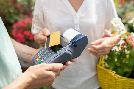 Contemporary female buyer using credit card to pay for some fresh potted flowers Imagens