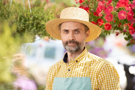 Mature gardener in hat and apron standing among flowers in bloom