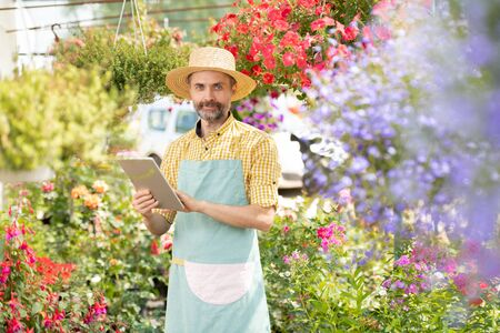 Mature bearded gardener in workwear searching for online information