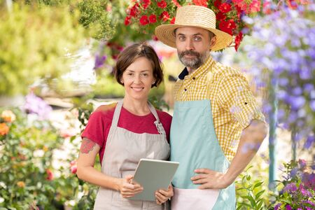 Two successful farmers in workwear standing among blooming flowers Stock Photo