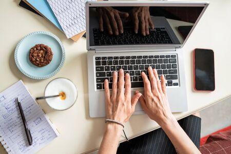 Overzicht van menselijke handen op laptoptoetsenbord tijdens netwerk per bureau Stockfoto