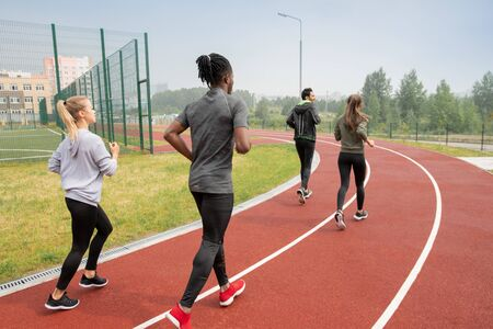 Rear view of young intercultural people in activewear running down race track Standard-Bild